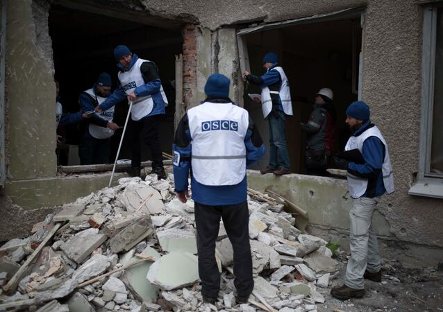 Organization for Security and Co-operation in Europe (OSCE) monitors investigate outside a kindergarten damaged in Saturday's shelling in which scores of people were killed and injured in Mariupol