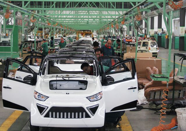 Workers assemble electric cars in a factory in Zouping, east China's Shandong province on September 16, 2014