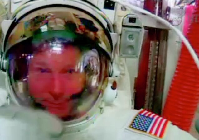 In this screenshot from a video provided by NASA, astronaut Terry Virts points to his helmet as he sits inside the International Space Station Wednesday during an inspection for water in his suit.