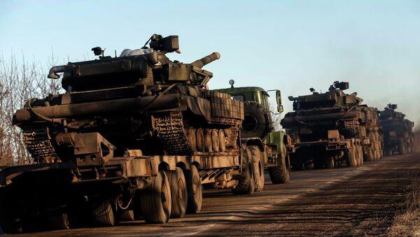 Military trucks from the Ukrainian armed forces transport tanks on the road near Artemivsk, eastern Ukraine, February 24, 2015 - Sputnik International