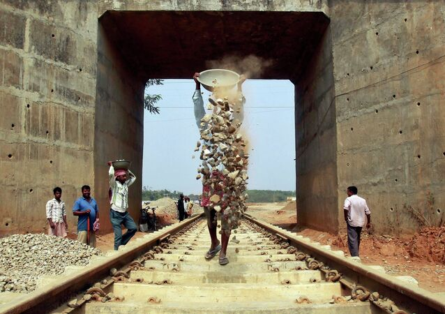 Labourers work at the installation site of a new railway track on the outskirts of Agartala, capital of India's northeastern state of Tripura February 25, 2015