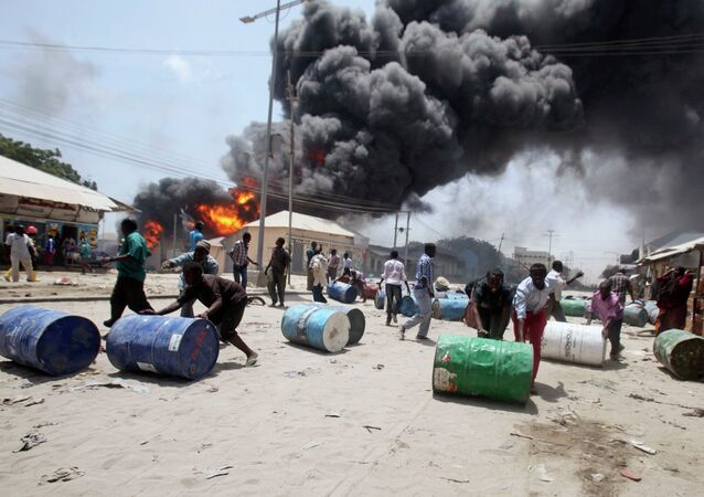 People push oil barrels away from the site of an explosion at a petrol station and storage facility near the Bakara open-air market in Somalia's capital Mogadishu, February 23, 2015