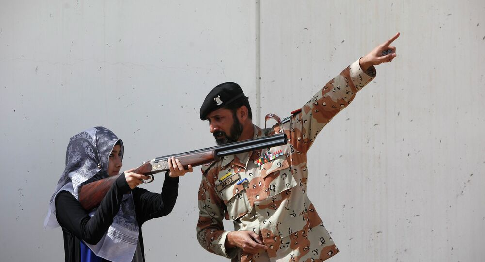 Pakistan Rangers soldier gestures as he instructs a female student of Nadirshaw Eduljee Dinshaw (NED) University during a counter-terrorism training demonstration at the Rangers Shooting & Saddle Club (RSSC) on the outskirts of Karachi, February 24, 2015