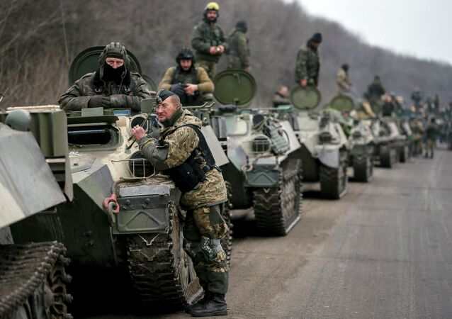 Members of the Ukrainian armed forces and armoured personnel carriers are seen preparing to move as they pull back from Debaltseve region, near Artemivsk