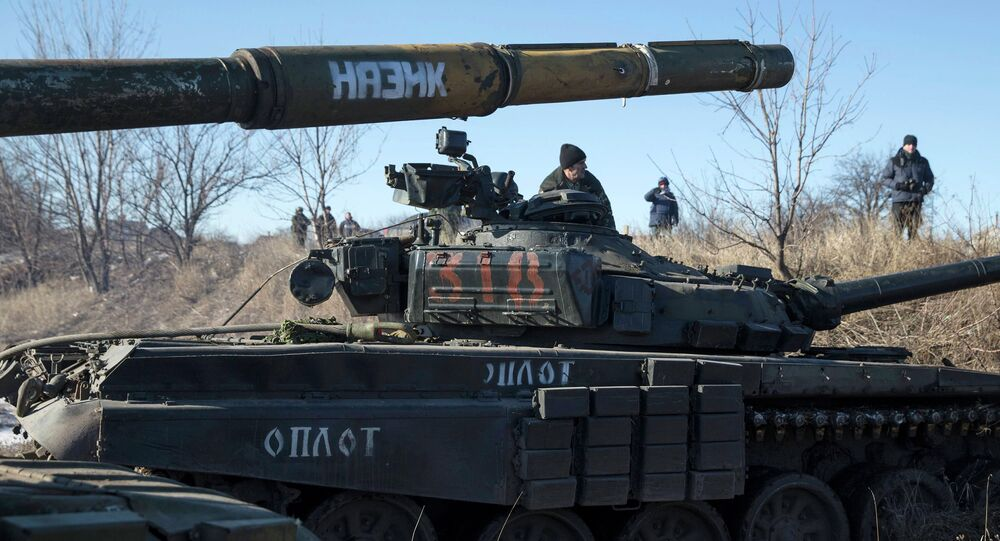 A tank crew member of the self-proclaimed Donetsk People's Republic Army sits on top of a tank at a checkpoint on the road from the town of Vuhlehirsk to Debaltseve