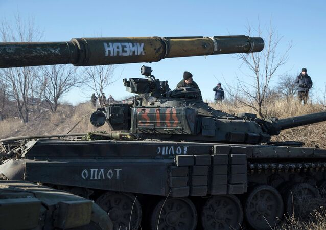 A tank crew member of the separatist self-proclaimed Donetsk People's Republic Army sits on top of a tank at a checkpoint on the road from the town of Vuhlehirsk to Debaltseve