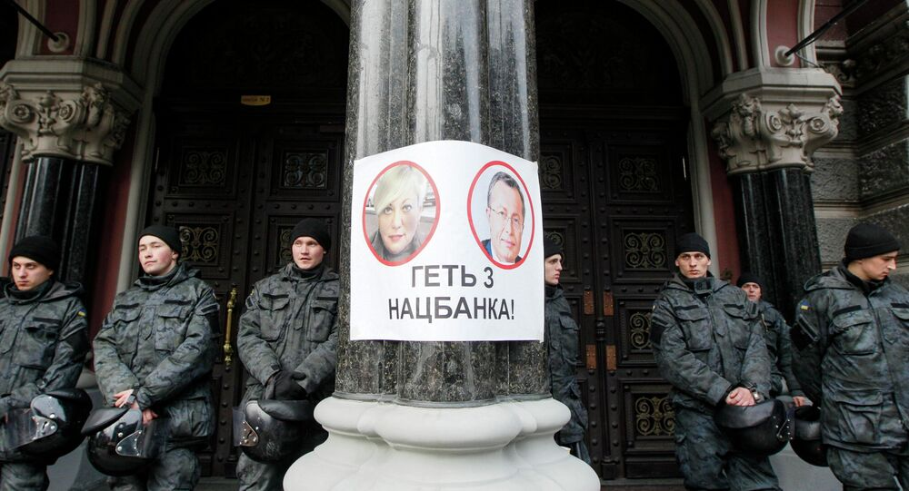 Policemen stay at the entrance of Ukraine's central bank office behind a poster depicting bank chief Valeria Gontareva (L) and the bank's first deputy Oleksandr Pysaruk in Kiev