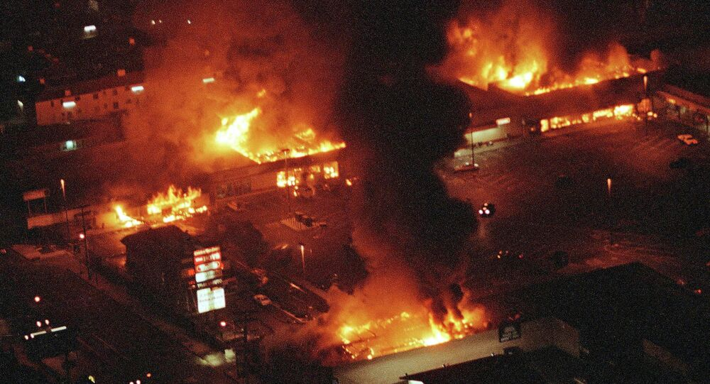 Several buildings in a Los Angeles shopping center fully engulfed in flames during the 1992 riots.