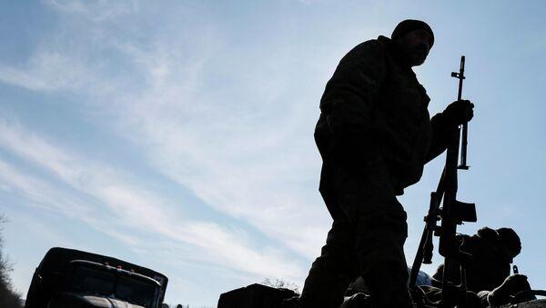 A member of the Ukrainian armed forces stands at an armoured personnel carrier near Artemivsk, eastern Ukraine - Sputnik International