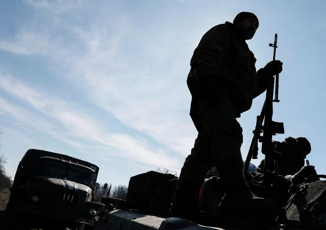 A member of the Ukrainian armed forces stands at an armoured personnel carrier near Artemivsk, eastern Ukraine