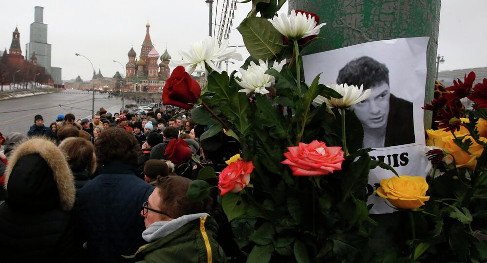 People gather at the site where Boris Nemtsov was recently murdered, with St. Basil's Cathedral and the Kremlin seen in the background, in central Moscow, February 28, 2015.