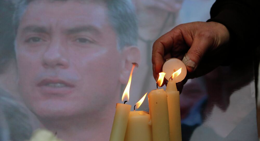 People light candles in memory of Boris Nemtsov, seen behind, at the monument of political prisoners 'Solovetsky Stone' in central St.Petersburg, Russia, Saturday, Feb. 28, 2015.