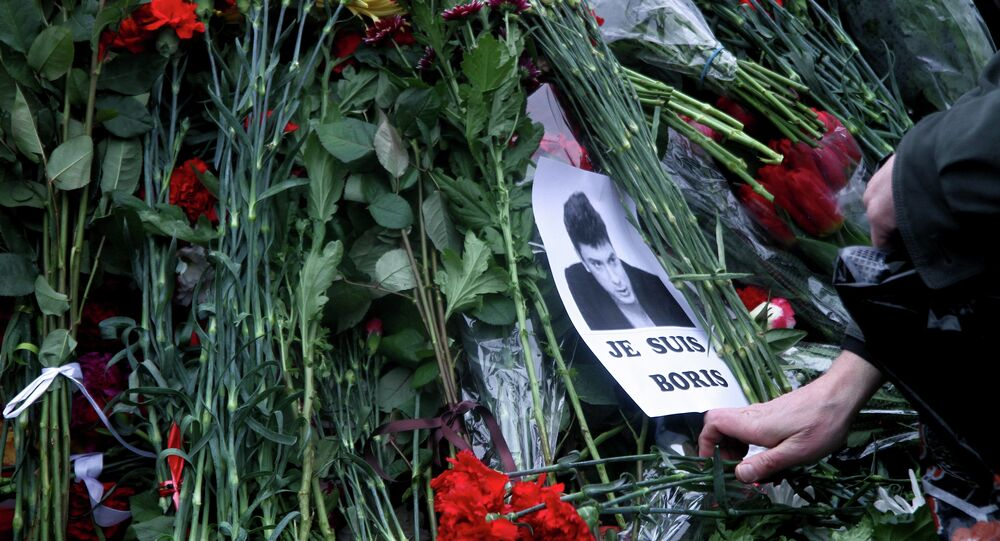 People place flowers on February 28, 2015 at the spot, where Russian opposition leader Boris Nemtsov was shot dead, near Saint-Basil's Cathedral, in the center of Moscow