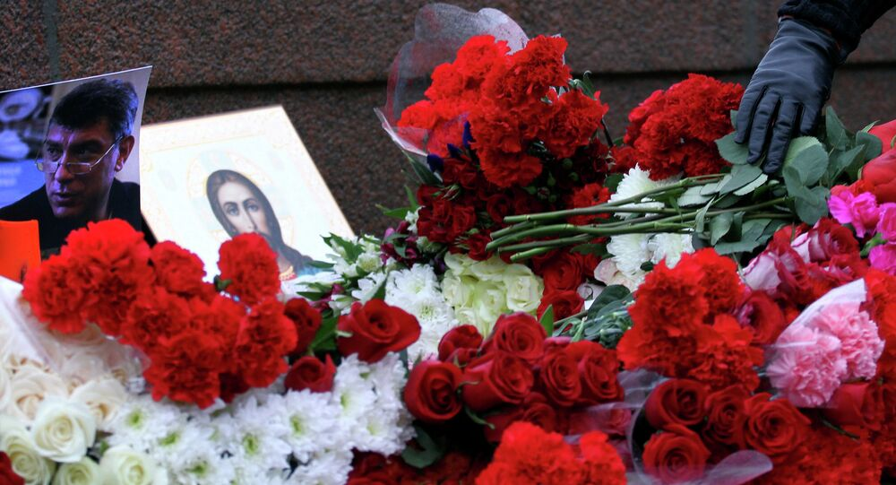 People place flowers on February 28, 2015 at the spot, where Russian opposition leader Boris Nemtsov was shot dead, near Saint-Basil's Cathedral, in the center of Moscow.