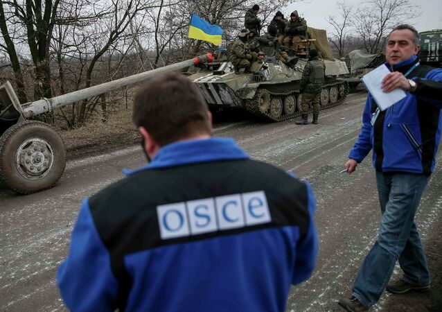 Members of Special Monitoring Mission of the Organization for Security and Cooperation (OSCE) to Ukraine walk along a convoy of Ukrainian armed forces in Paraskoviyvka, eastern Ukraine