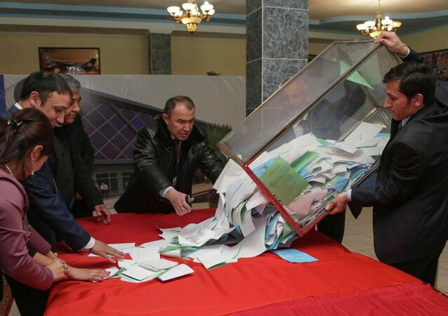 A member of a local electoral commission empties a ballot box after a parliamentary election at a polling station in the Tajik capital Dushanbe