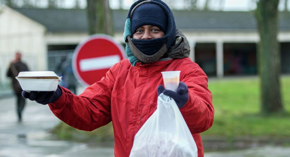 A migrant holds up hot food received from the association La Vie Active in Calais on January 15, 2015, at the site where a new day center for migrants was opened.