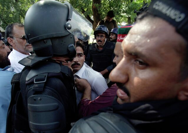 Pakistani police officers push anti-government activists.