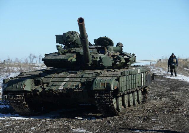 A self-defender of the Lugansk People's Republic near a captured T-64 tank in Debaltsevo.