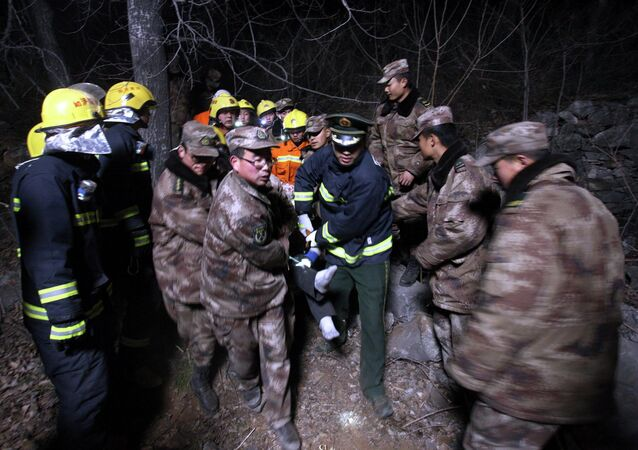 Rescue workers remove an injured person from the site after a bus accident in Henan province, March 3, 2015