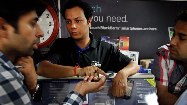 An Indian shopkeeper, center, tries to sell a Nokia mobile phone to a customer, left, in New Delhi, India - Sputnik International