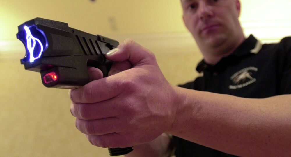 Clay Winn, of TASER International, demonstrates the company's Advanced M-26 model during a news conference in Las Vegas