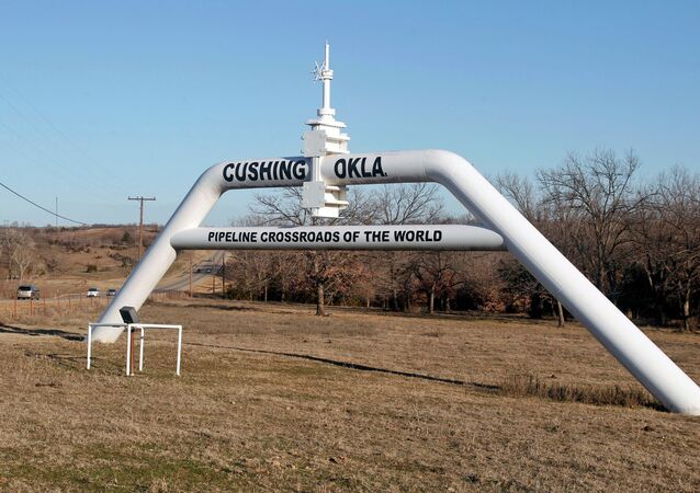 This Wednesday, Feb. 1, 2012 photo shows a marker declaring Cushing, Okla. as the pipeline crossroads of the world, in Cushing. For the past seven weeks, the United States has been producing and importing an average of 1 million more barrels of oil every day than it is consuming.