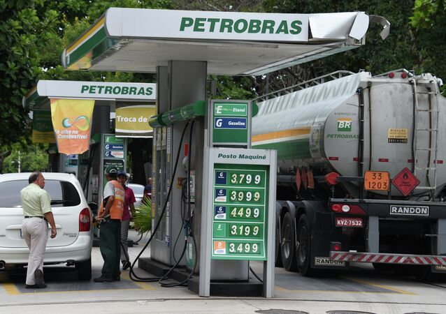 A man fuels up his car at a Petrobras station in downtown Rio de Janeiro
