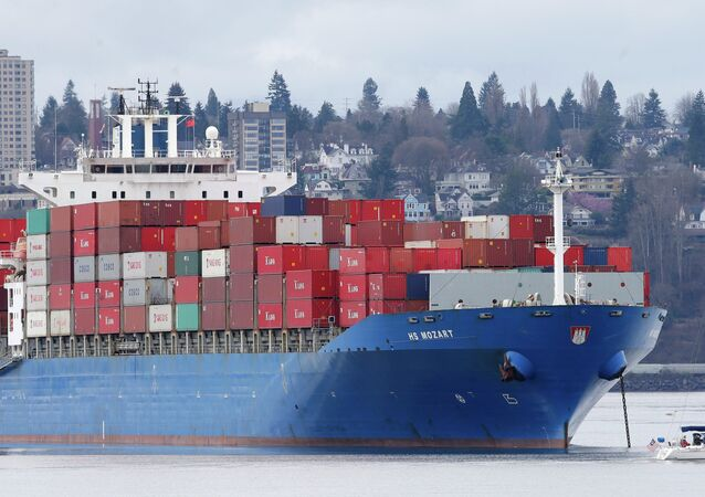 A sailboat moves past the 925-foot long HS Mozart cargo ship in Tacoma, Wash. File photo