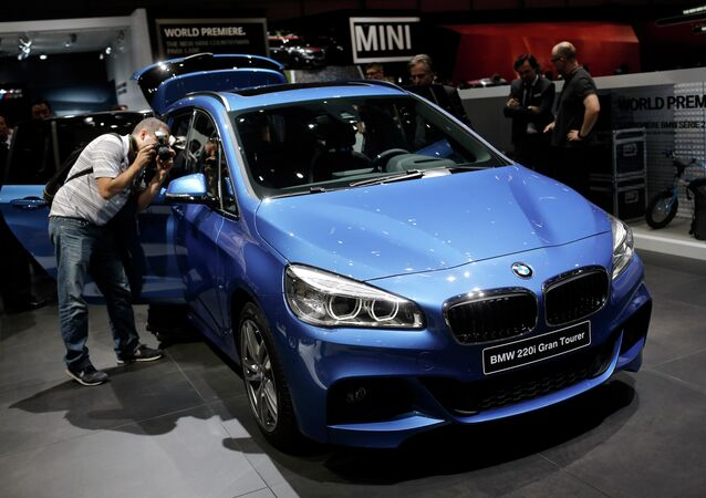 Journalists take pictures of the BMW 220i Gran Tourer during the first press day of the Geneva International Motor Show