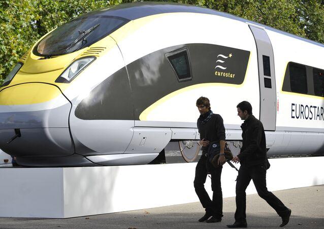 Pedestrians walk by a mock up of an Eurostar 320 high speed train in central London