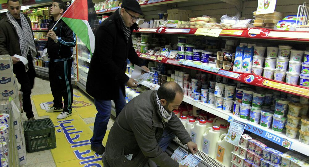 A Palestinian activist places a sign to boycott Israeli products at a supermarket in Bethlehem, West Bank. Most West Bank shops no longer carry the products of six major Israeli food companies, as a boycott triggered by rising Israeli-Palestinian tensions is taking hold, a boycott leader said Sunday, March 1, 2015. Activists in the Fatah movement of Palestinian President Mahmoud Abbas announced the boycott plans last month, after Israel halted transfer of vital tax revenues to Abbas' cash-strapped Palestinian Authority.