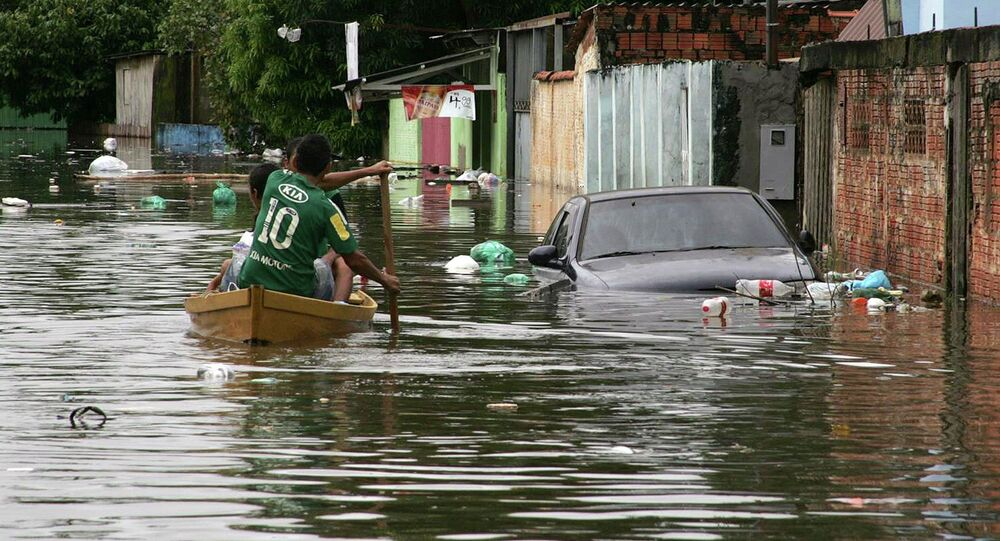 Residents row their boat in a neighbourhood flooded by the Acre river, which continues to rise from weeks of heavy rainfall in the region including northern Bolivia, in Rio Branco, Acre state