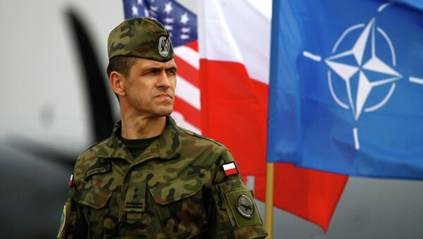 A Polish soldier stands near US and Poland's national flags and a NATO flag in Swidwin, northern west Poland, April 23, 2014 - Sputnik International