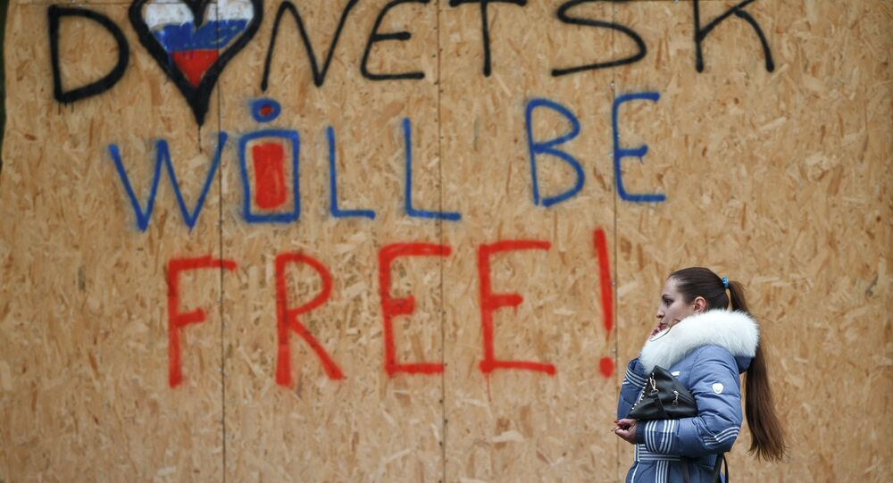 A woman walks by shop windows protected from possible shelling with wooden boards with the inscription Donetsk will be free in Donetsk, Ukraine, Sunday, March 1, 2015
