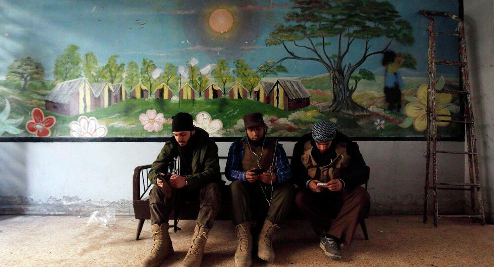 Rebel fighters of 'Al-Sultan Murad' brigade use their mobile phones inside a room near the frontline in Handarat area, north of Aleppo March 1, 2015