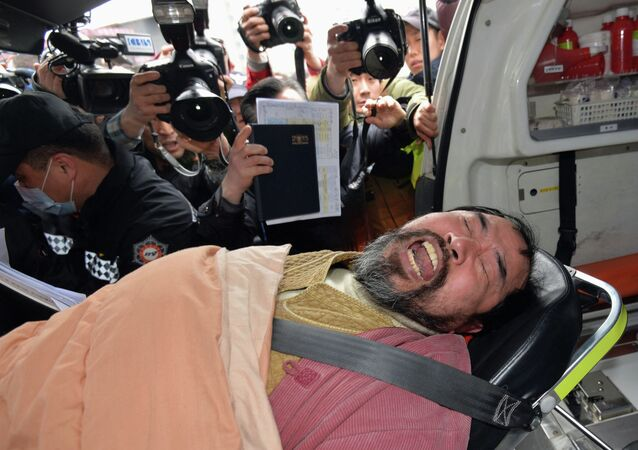Kim Ki-jong, a member of a pro-Korean unification group who attacked the U.S. ambassador to South Korea Mark Lippert at a public forum, is carried on a stretcher off an ambulance as he arrives at a hospital in Seoul