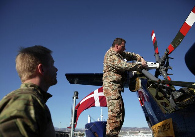 Danish soldiers from the Royal Danish Navy work at an helicopter onboard of the Absalon military ship in the Cypriot port city of Limassol