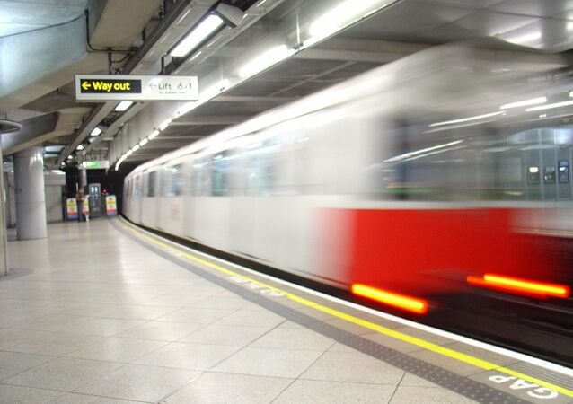A District line tube train leaving Westminster station
