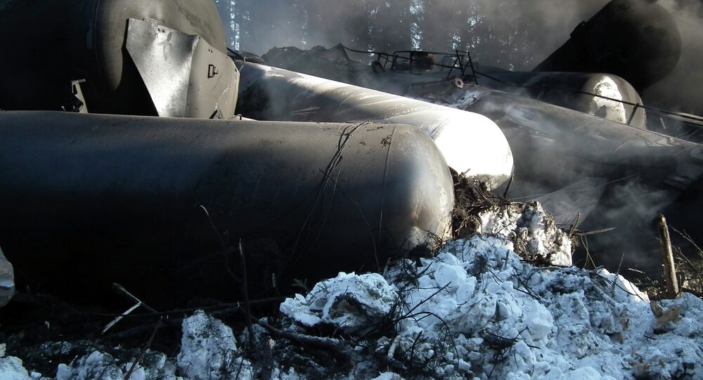 Tanker rail cars are seen lying on their side after a crude oil train derailment
