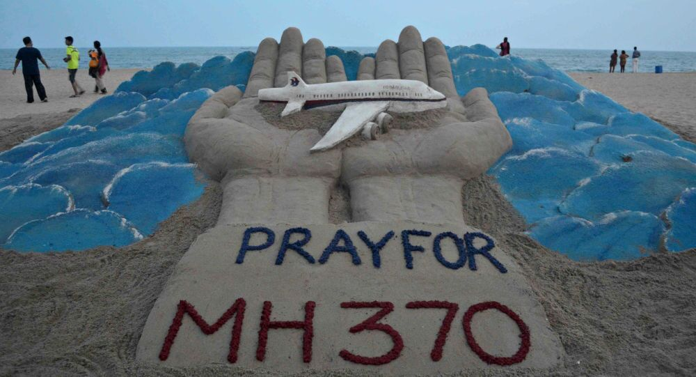 Beachgoers walk past a sand sculpture made by Indian sand artist Sudersan Pattnaik with a message of prayers for the missing Malaysian Airlines flight MH370