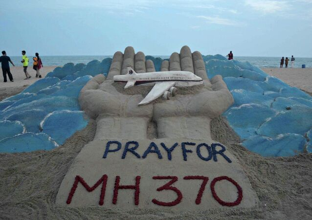 Sand sculpture made by Indian sand artist Sudersan Pattnaik with a message of prayers for the missing Malaysian Airlines flight MH370