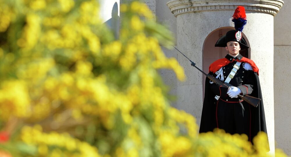 A female member of the Italian Presidential Honor Guard stands at the entrance of the Quirinale Palace, the Italian Presidential palace, decorated with yellow mimosa on the occasion of the International Women's day