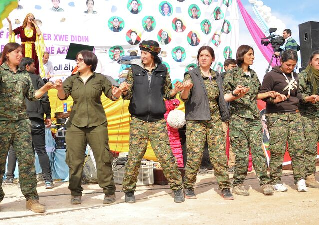 Women fighters from the People's Protection Units (YPG) dance during festivities on the eve of International Women's Day in Syria's northeastern city of Qamishli in the Hasakeh province, on the border with Turkey