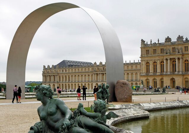 Visitors walking under The Arch of Versailles, a work of art by Korean artist Lee Ufan, displayed in the gardens of the Versailles Castle, west of Paris, France.