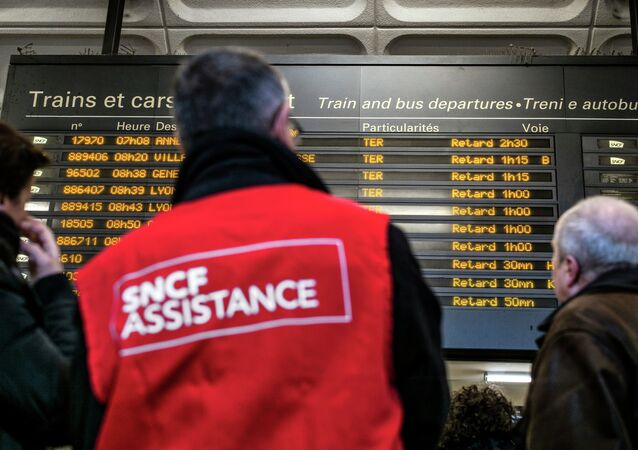 People stand next to a member of SNCF customer service staff in front of a board displaying departure information indicating that all trains have been delayed at Lyon-Part-Dieu railway station in Lyon