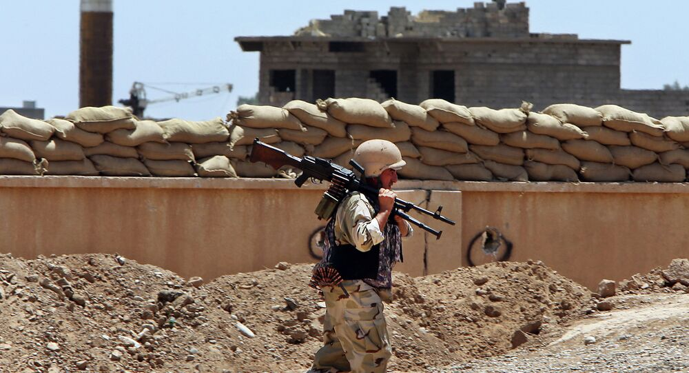 A Kurdish Peshmerga fighter carries his weapon walks onto his base, where two flags of the Islamic State in Iraq and the Levant (ISIL) are seen on a building, right, and water tower, left, at the front line with the al-Qaida-inspired militants in Tuz Khormato, 100 kilometers (62 miles) south of the oil rich province of Kirkuk, northern Iraq.