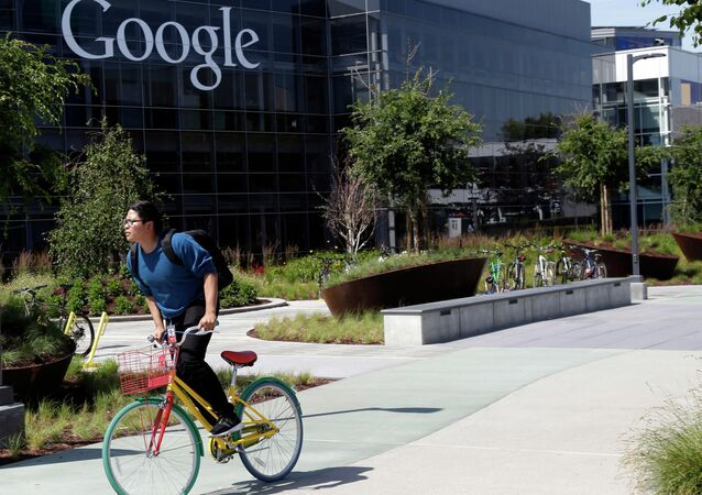 In this June 5 photo, a man rides a bike past a Google sign at the company's headquarters in Mountain View, California.