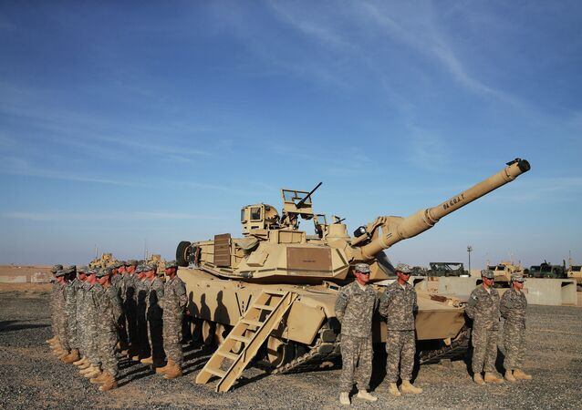 US troops stand to attention next to an Abrams tank in Camp Buehring in the northwest of Kuwait