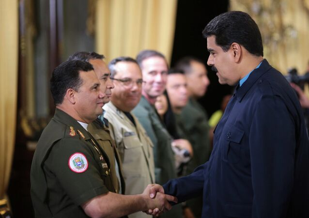 Venezuela's President Nicolas Maduro (R) greets Gustavo Gonzalez as he welcomes army members sanctioned by the U.S. during a national TV broadcast in Caracas in this March 9, 2015 picture provided by Miraflores Palace.